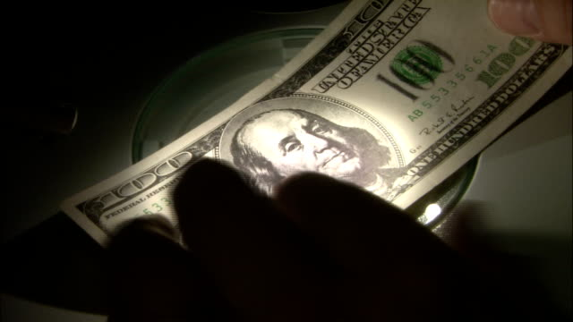a man examines an american bill under a light. - anpassen stock-videos und b-roll-filmmaterial