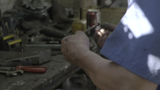 man examines metal rod - workbench stock videos & royalty-free footage