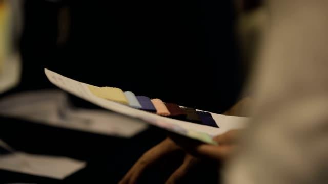 a man examining fabric swatches - ornato video stock e b–roll