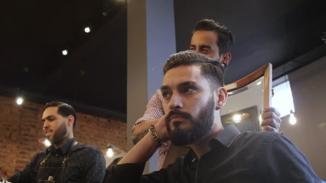 Mann seinem neuen Look nach Haarschnitt im Salon untersuchen