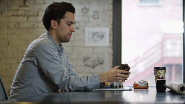 MS DS Man examining machine part at desk / Salt Lake City,Utah,USA