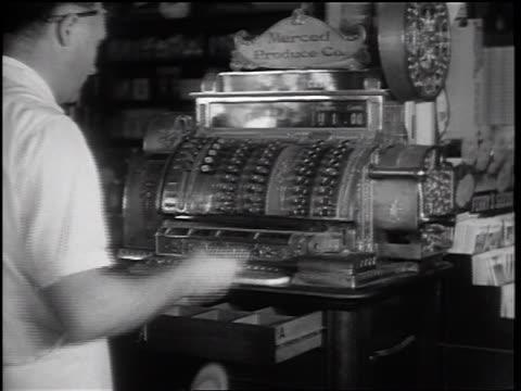 B/W 1932 REAR VIEW man examining + placing scrip it in cash register drawer + closing register