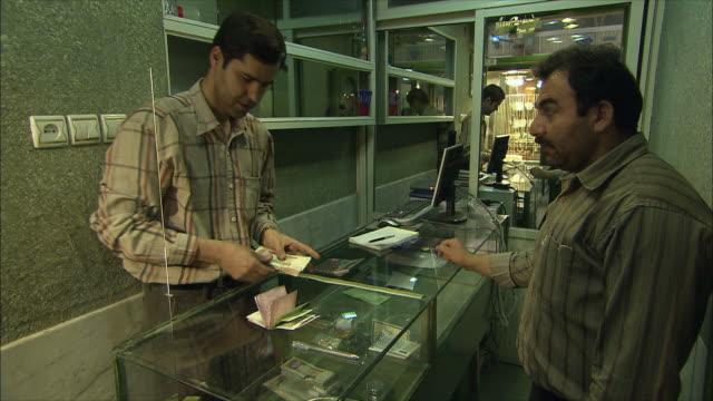 vídeos de stock, filmes e b-roll de ms man exchanging money in currency exchange, grand bazaar, isfahan, iran - casa de câmbio