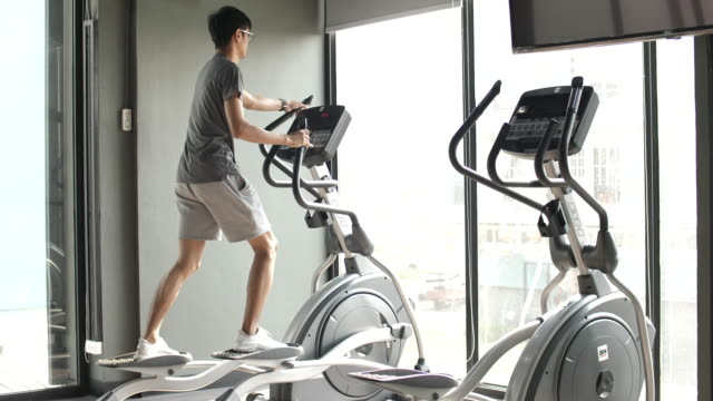 man exercise on elliptical in gym - cross trainer stock videos & royalty-free footage