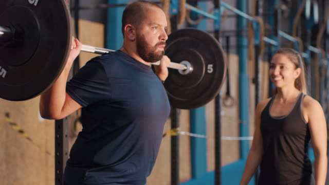vídeos de stock, filmes e b-roll de a man exercises in a gym with a female trainer - incentivo