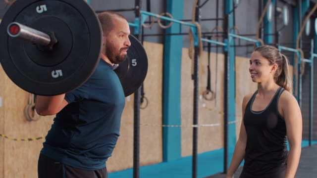 a man exercises in a gym with a female trainer - bronek kaminski stock videos & royalty-free footage