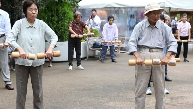 man exercises with a wooden dumbbell during an event marking respect for the aged day at a temple in the sugamo district of tokyo, japan, on monday,... - 老化点の映像素材/bロール