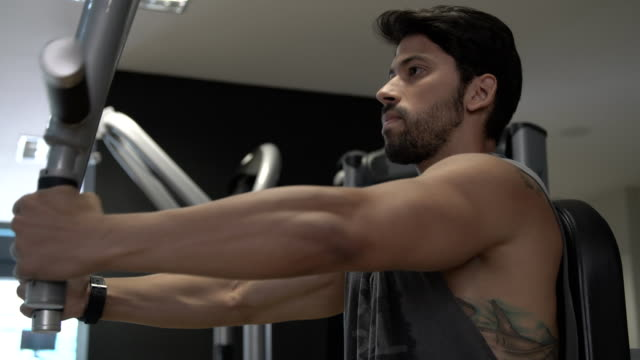 Man exercising arms and back in fitness