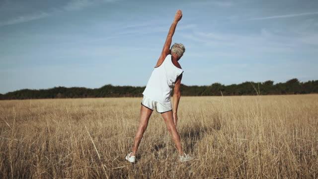 stockvideo's en b-roll-footage met ws man exercising in field / corsept, loire-atlantique, france - alleen één seniore man