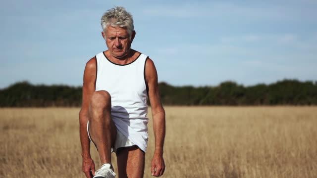 stockvideo's en b-roll-footage met ms man exercising in field / corsept, loire-atlantique, france - alleen één seniore man