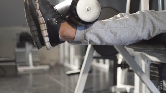 man exercising leg with gym machine