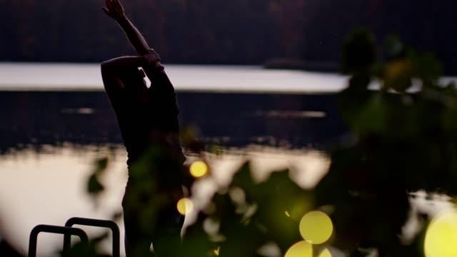 男は桟橋で行使。湖の夕日 - リフレクション湖点の映像素材/bロール