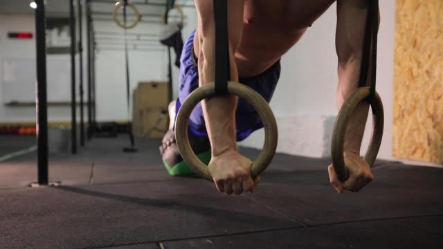 Man uitoefenen op gymnastiek ringen