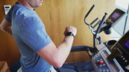 Man Exercising On Treadmill At Home Checking Smart Watch