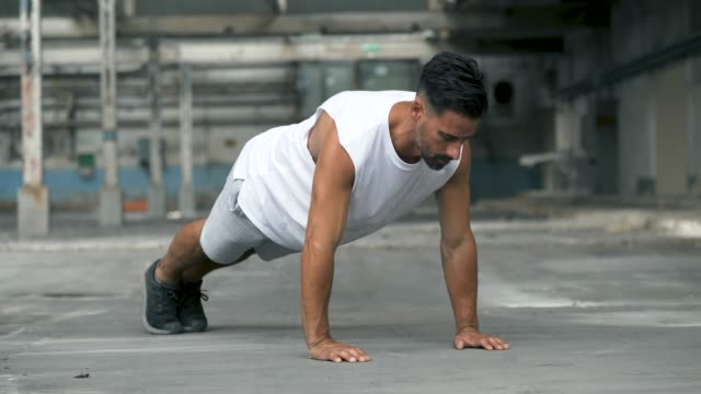 vídeos de stock e filmes b-roll de man exercising push ups in an abandoned warehouse - homens adultos