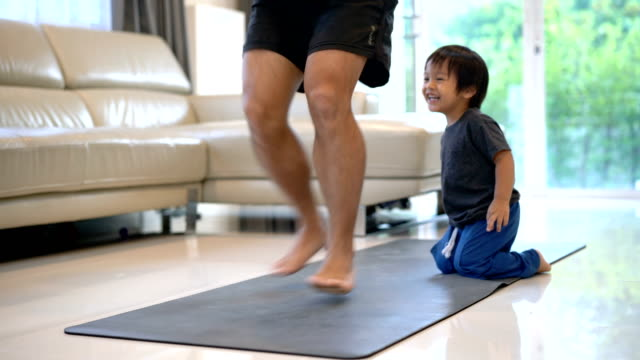 man exercising with baby boy at home. - relaxation exercise stock videos & royalty-free footage