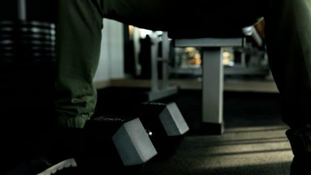 Mann Trainieren mit Hanteln im Fitnessstudio