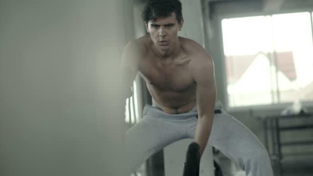 Mann mit Seilen im Fitness-Studio trainieren