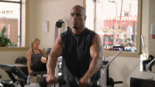 ms, man exercising with weights in gym, woman in background, garwood, new jersey, usa - hand weight stock videos & royalty-free footage