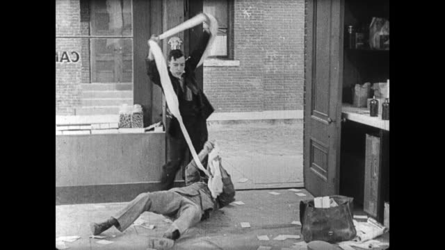 1922 man (buster keaton) exerts himself stretching candy before hitting surprised mailman in face with candy and walking away - pulling stock videos & royalty-free footage