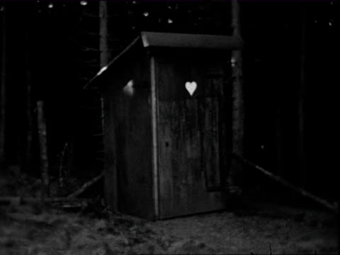 1938 b/w montage man exiting outhouse in woods, smiling to camera / thuringia, germany  - toilet stock videos and b-roll footage