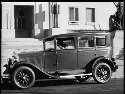b/w 1928 man exiting pontiac car in front of building (2 shots) / industrial - 1928 stock-videos und b-roll-filmmaterial
