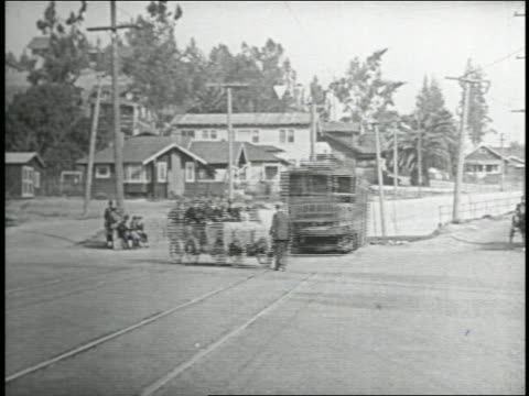 b/w 1935 man exiting trolley knocked over by keystone kops driving police truck / man getting up - 1935 stock videos & royalty-free footage