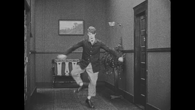 1918 a man (al st john) exits a hotel room and dances - eccitazione video stock e b–roll
