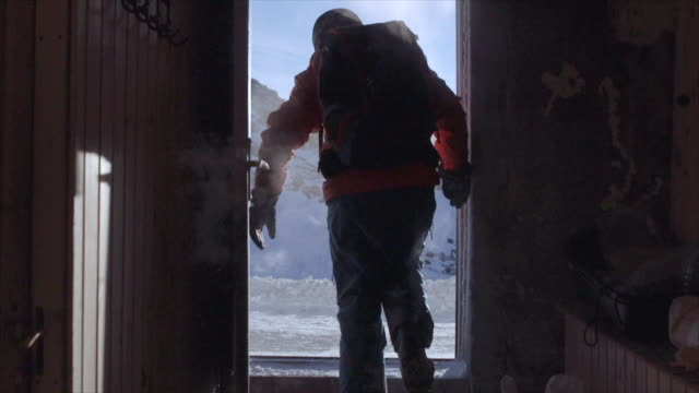 a man exits a ski hut shelter in snow covered mountains. - slow motion - sports equipment stock videos & royalty-free footage