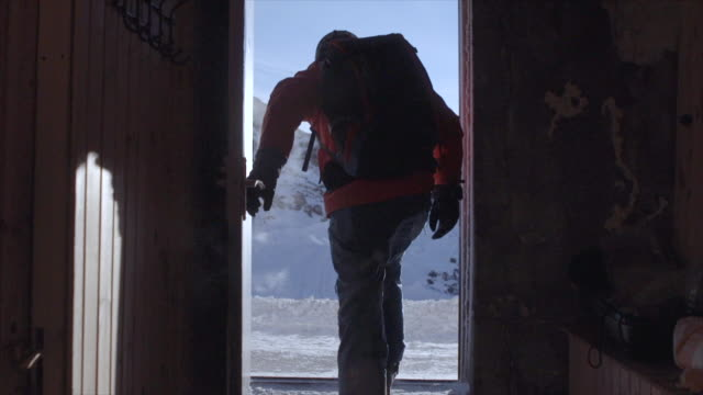 a man exits a ski hut shelter in snow covered mountains. - slow motion - russia stock videos & royalty-free footage