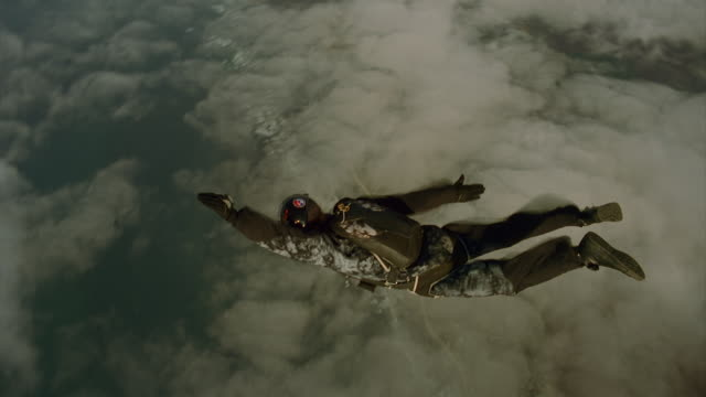 vídeos de stock, filmes e b-roll de man exits airplane and flies over the ocean - paraquedismo
