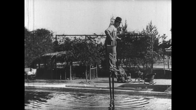 1921 a man exits from a pool on stilts - stilts stock videos and b-roll footage