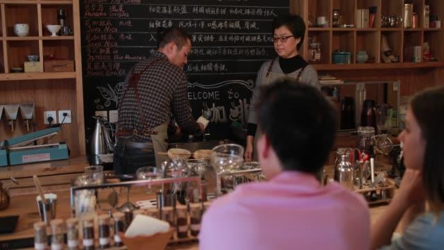 mann, kunden zu erklären, wie er die zubereitung von kaffee - chinesischer abstammung stock-videos und b-roll-filmmaterial