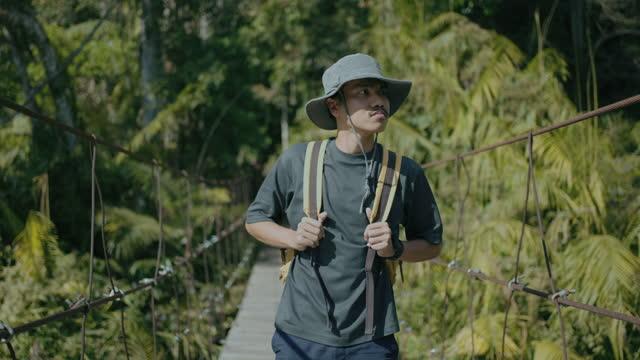 vídeos de stock e filmes b-roll de man explorer walking on rope bridge in forest - ponte suspensa