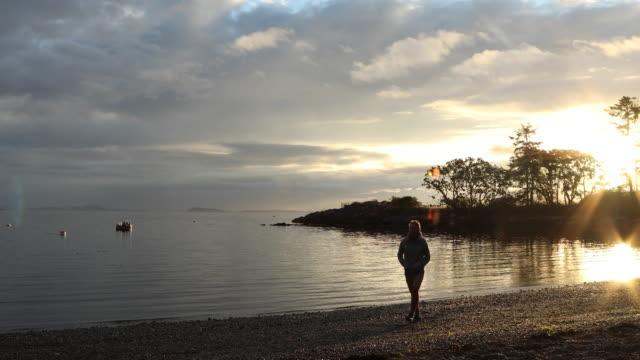 Man utforskar beach kusten vid soluppgången, ocean avlägsen