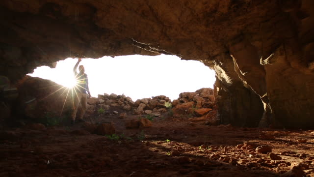 man explores cave opening, interior, sunrise - impressionante video stock e b–roll