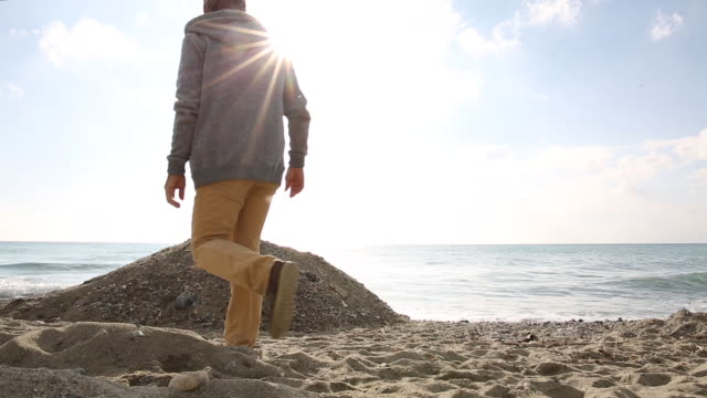 man explores coastal beach area, surf behind - only mature men stock videos & royalty-free footage