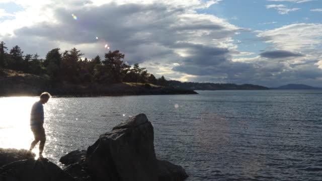 Man utforskar kustlinje vid soluppgången, ocean avlägsen