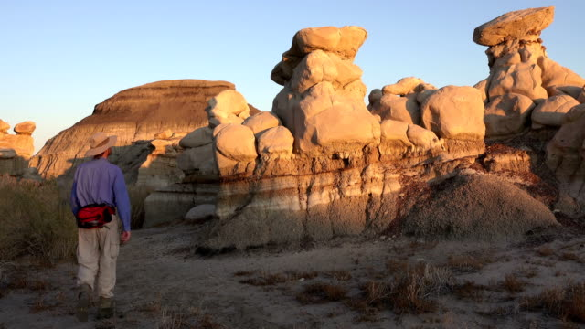 man explores eroded cretaceous sandstone hoodoos bisti de-na-zin wilderness new mexico - bisti badlands stock videos & royalty-free footage