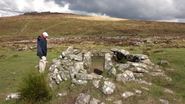 man explores prehistoric circular village grimspound dartmoor national park devon england uk - dartmoor stock videos & royalty-free footage
