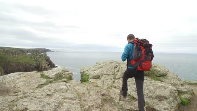 vidéos et rushes de homme explorant cornwall au royaume-uni - falaise