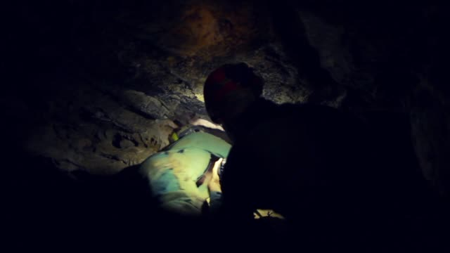 man exploring dark cave with flashlight - miniera video stock e b–roll