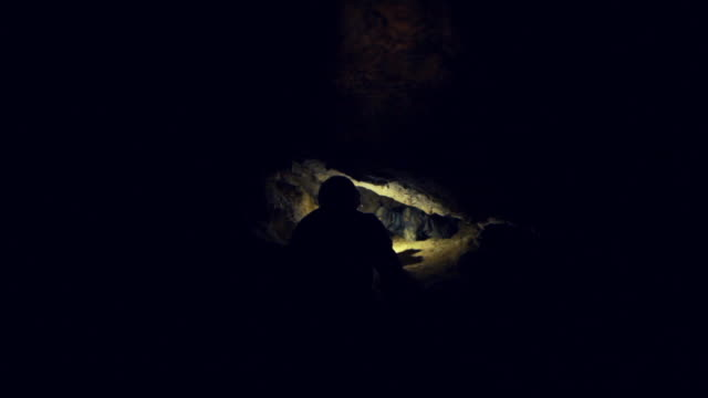 man exploring dark cave with flashlight - miner stock videos and b-roll footage