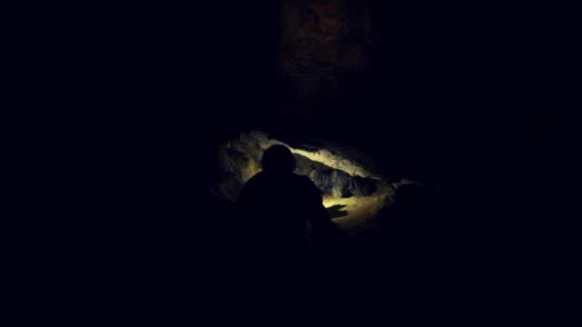 Man exploring dark cave with flashlight