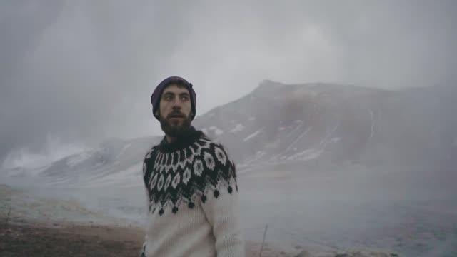 vídeos y material grabado en eventos de stock de hombre explorando hverir en islandia en invierno - géiser