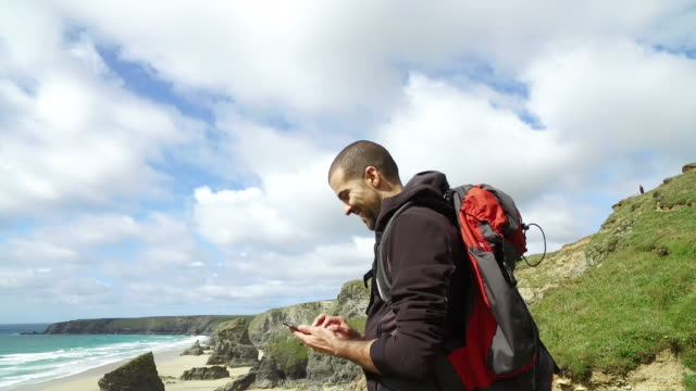 man exploring the wild nature in uk - cornwall. 4k video - rucksack stock videos and b-roll footage