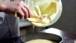Man extracting liquid cake batter from mixing bowl. Baking cake. Home baking