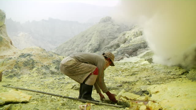 MS Man extracting sulfur from the Ijen volcano complex near toxic cloud / Ijen, Java, Indonesia