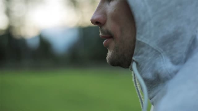 Man face head jogging close up slow motion outdoors green park background shallow macro. Sportsman in 30s runs in morning nature thinking dreaming making plans work future conscious look freedom eyes