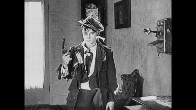 1922 Man (Buster Keaton) fails at his attempt to shoot himself, so his girlfriend's father kicks him through a window